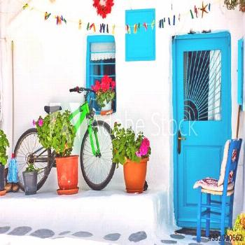 Street with whitewashed house and bicycle in Mykonos ,